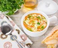 Sopa italiana con las pastas del orzo Sopa en un cántaro blanco, cuenco del orzo del pollo en fondo de madera Imagen de archivo