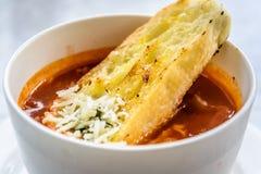 Sopa italiana del minestrone con pan de ajo y queso cheddar rallado Foto de archivo