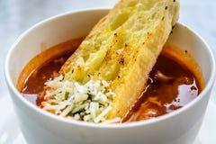 Sopa italiana del minestrone con pan de ajo y queso cheddar rallado Fotos de archivo