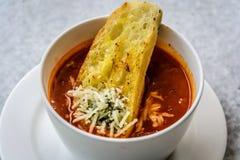 Sopa italiana del minestrone con pan de ajo y queso cheddar rallado Fotografía de archivo