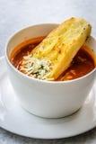Sopa italiana del minestrone con pan de ajo y queso cheddar rallado Imagen de archivo libre de regalías