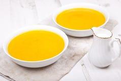 Sopa ligeramente condimentada de la zanahoria en cuencos, en la tabla blanca imagen de archivo libre de regalías