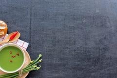 Sopa, pan y verduras verdes sobre la tabla negra Fotos de archivo