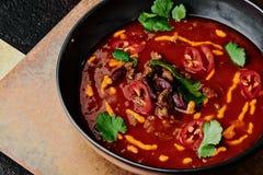 Sopa picante do tomate com feijões, pimenta de pimentão, queijo e salsa em uma placa preta em um fundo de cobre fotos de stock