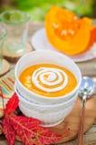 Sopa poner crema de la calabaza con crema agria en un cuenco blanco Fotografía de archivo