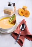 Sopa poner crema de la calabaza con la tostada del parmesano en una placa blanca Foto de archivo libre de regalías