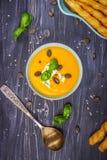 Sopa poner crema de la calabaza y de la zanahoria con las semillas de calabaza y el queso verde en un fondo de madera Imagen de archivo