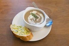 Sopa poner crema de la seta en el cuenco blanco con pan de ajo Imagenes de archivo