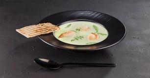 Sopa poner crema del bróculi con el camarón en una placa negra hermosa en un fondo oscuro Plato de los mariscos Foco selectivo foto de archivo