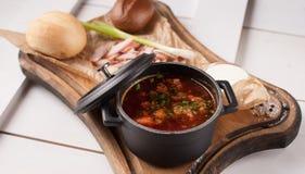 Sopa roja del borsch en un pequeño cazo colocado en los tableros blancos Fotos de archivo libres de regalías