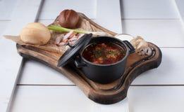 Sopa roja del borsch en un pequeño cazo colocado en los tableros blancos Imágenes de archivo libres de regalías