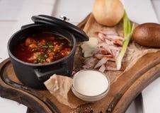 Sopa roja del borsch en un pequeño cazo colocado en los tableros blancos Cierre para arriba Imagenes de archivo