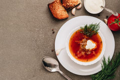 Sopa roja en la placa blanca en fondo gris Borsch fresco con la tostada tostada foto de archivo libre de regalías