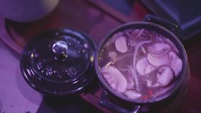 Sopa sabrosa con las setas y los tallarines en el cuenco del metal con una tapa en la tabla en el club nocturno en primer ligero  metrajes