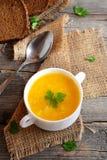 Sopa simple de la calabaza con las patatas y el arroz Sopa en un cuenco, cuchara, rebanadas de la calabaza del pan marrón en viej Imagen de archivo