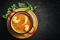 Sopa tailandesa tradicional com camarão em um potenciômetro vermelho com salsa fotografia de stock