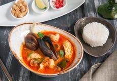 Sopa tradicional Tom Yam de Tailândia Com camarões, mexilhões, carne da vieira, arroz e as especiarias quentes fotos de stock