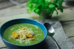 Sopa triturada fresca con br?culi y habas verdes en una placa azul en un fondo de madera imagen de archivo libre de regalías