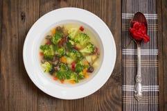 Sopa vegetal com brócolis, cogumelos e ervas Fundo de madeira Vista superior Close-up Fotografia de Stock