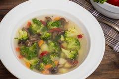 Sopa vegetal com brócolis, cogumelos e ervas Fundo de madeira Vista superior Close-up Foto de Stock Royalty Free