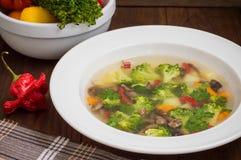 Sopa vegetal com brócolis, cogumelos e ervas Fundo de madeira Vista superior Close-up Fotografia de Stock Royalty Free