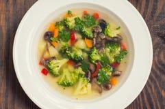 Sopa vegetal com brócolis, cogumelos e ervas Fundo de madeira Vista superior Close-up Fotos de Stock Royalty Free