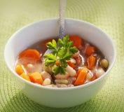 Sopa vegetal com feijão e cenouras no fundo verde Fotos de Stock Royalty Free