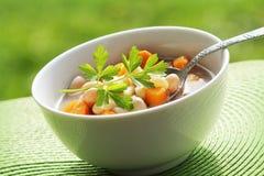 Sopa vegetal com feijão e cenouras no fundo verde Fotografia de Stock Royalty Free