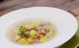 Sopa vegetal dos grãos-de-bico com o alho-porro, as batatas e o bok choy Imagem de Stock