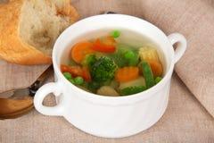Sopa vegetal, fatias de pão e colher Imagem de Stock