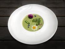 A sopa vegetal triturou ervilhas verdes e brócolis, decorados com flores e as ervas perfumadas Apreciou o prato Foto de Stock Royalty Free