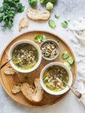 Sopa vegetal verde del vegano del keil, de las coles de Bruselas, del calabacín, del puerro con las diversas semillas germinadas  fotos de archivo