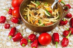 Sopa vegetariana densa con las pastas en cuenco de cerámica, tomate crudo y chiles alrededor imagen de archivo