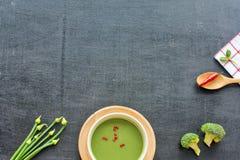 Sopa verde, cebolla, bróculi, chile en una tabla negra Foto de archivo libre de regalías