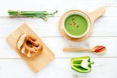 Sopa verde del puré, pan y verduras verdes en una tabla blanca Imagen de archivo libre de regalías