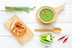 Sopa verde del puré, pan y verduras verdes en una tabla blanca Imágenes de archivo libres de regalías