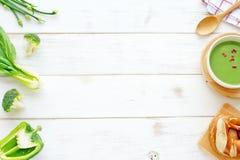 Sopa verde del puré, pan y verduras verdes en una tabla blanca Foto de archivo