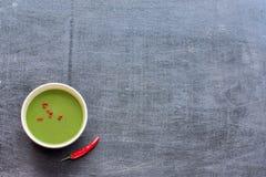 Sopa verde picante en una tabla negra Imagen de archivo