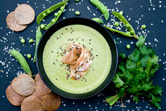 Sopa verde sana con el jamón y los guisantes en un fondo Imágenes de archivo libres de regalías