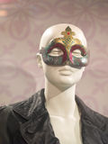 Sophisticated. Bald female mannequin dressed in an intricate mask and black shirt against a floral backdrop Royalty Free Stock Images