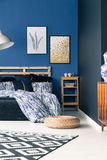 Sophisticated bedroom with blue walls. Sophisticated bedroom with elegant blue walls, carpet, pouf and posters Royalty Free Stock Image