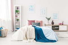 Sophisticated bedroom interior with posters. Blue blanket on bed with pink cushions in sophisticated bedroom interior with posters and basket Stock Photos