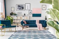 Sophisticated blue living room interior. Copper table near navy blue sofa and armchair in sophisticated living room interior with posters Stock Photography