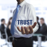 Sophisticated businessman holding the word trust Stock Photos