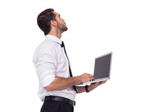Sophisticated businessman standing using a laptop. On white background Stock Photos
