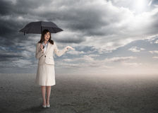 Sophisticated businesswoman holding an umbrella. During stormy weather Royalty Free Stock Photos