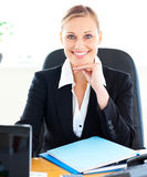 Sophisticated businesswoman smiling at the camera. Sophisticated caucasian businesswoman smiling at the camera in her office at her desk Royalty Free Stock Photography