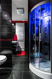 Sophisticated dark bathroom interior. Dark bathroom interior with black tiling and new hydromassage shower with blue led lighting Stock Photo