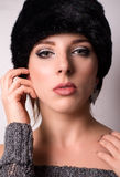 Sophisticated elegant woman in winter fashion. Sophisticated elegant young woman in elegant winter fashion wearing a fur hat and knitwear looking directly at the Royalty Free Stock Photo