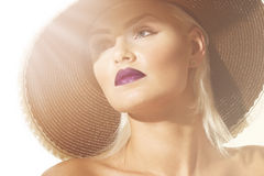 Sophisticated exotic young woman. Close up head shot of a gorgeous sophisticated exotic young blond woman wearing a wide brimmed hat facing into sun flare Royalty Free Stock Photography